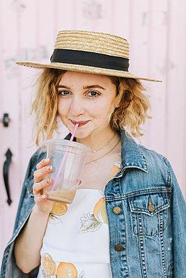 Young woman wearing boater drinking iced coffee, portrait, Menemsha, Martha's Vineyard, Massachusetts, USA - p924m2058151 by Lena Mirisola