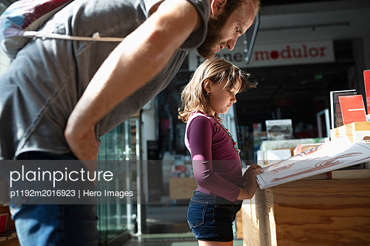 Father and daughter reading book in bookstore - p1192m2016923 by Hero Images