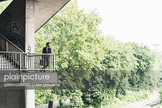 Businessman standing on stairs at underpass - p300m2004331 von Uwe Umstätter