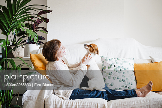 Senior woman playing with Jack Russell Terrier on sofa at home - p300m2265630 by Eva Blanco