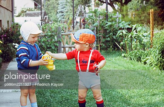 Geschwister spielen im Garten DDR  - p986m2211927 von Friedrich Kayser