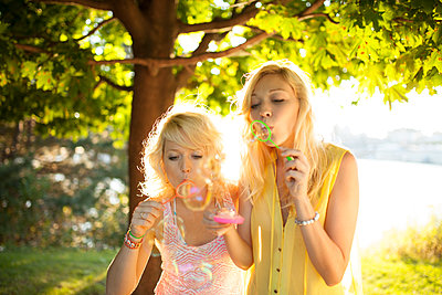 Young group of friends blowing bubbles in park at sunset - p1166m2071933 by Cavan Images