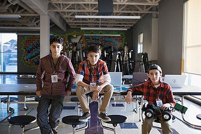 Portrait confident pre-adolescent boys with robotics in classroom - p1192m1231037 by Hero Images