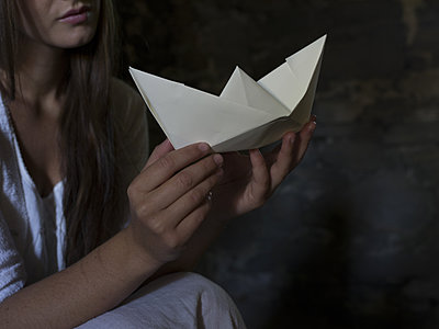 Young woman holding paper boat - p945m1154639 by aurelia frey