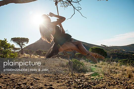 Brunette woman swings under tree - p1640m2264334 by Holly & John