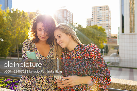 Female friends using smart phone against retaining wall in city - p300m2240782 by Ignacio Ferrándiz Roig