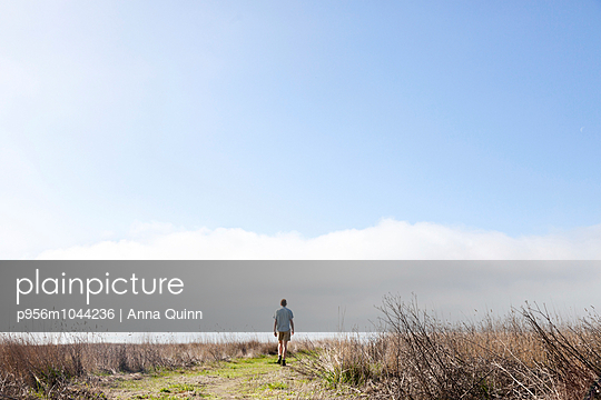 Man walking on field - p956m1044236 by Anna Quinn