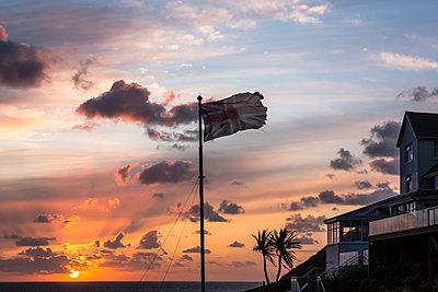 Tatty union jack near coastal hotel at sunset - p1057m2008610 by Stephen Shepherd