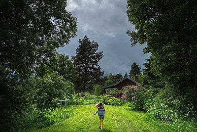 Girl running to a house - p1418m1571780 by Jan Håkan Dahlström