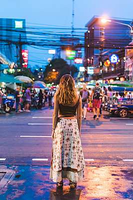 Thailand, Bangkok, young woman in the city standing on the street at night - p300m1580691 by VITTA GALLERY