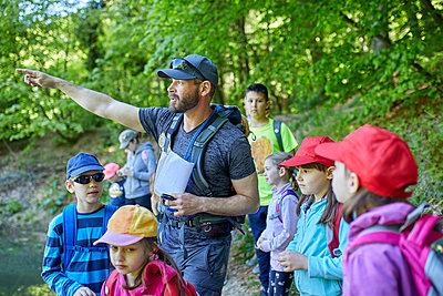 Man talking to kids on a field trip in forest - p300m1587848 von Zeljko Dangubic