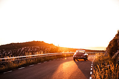Spain, classic car driving on road during sunset - p300m2078652 by Aitor Carrera Porté