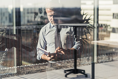 Mature businessman using cell phone behind windowpane - p300m2084058 by Uwe Umstätter