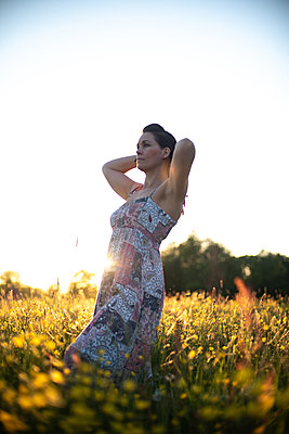 Woman standing in a meadow in summer - p310m2289407 by Astrid Doerenbruch