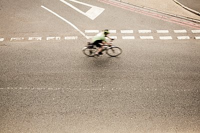 Overhead view of racing cyclist speeding on urban road in racing cycle race - p429m1118524f by Seb Oliver