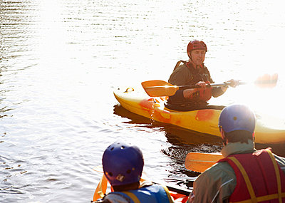 Teacher talking to students in kayaks - p429m665638f by Nick Daly