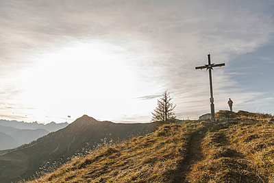 Silhouette of mid adult woman and wooden cross - p429m896507f by Alan Graf