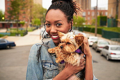 Black woman holding dog in city - p555m1304537 by Granger Wootz