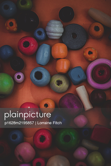 Coloured beads on plain coloured background - p1628m2195857 by Lorraine Fitch