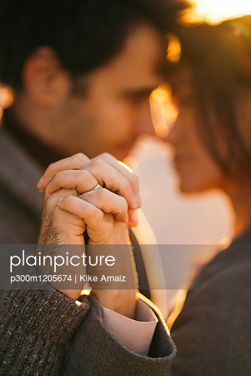 Couple holding hands at sunset, close-up