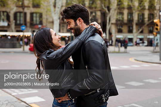 Spain, Barcelona, happy young couple hugging on the street - p300m2023805 von Mauro Grigollo