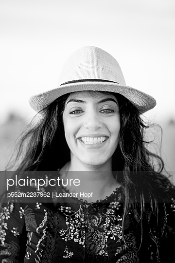 Happy woman with black hair and straw hat - p552m2287962 by Leander Hopf