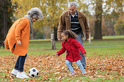 Grandparents playing soccer with granddaughter in autumn park - p1023m2161216 by Tom Merton