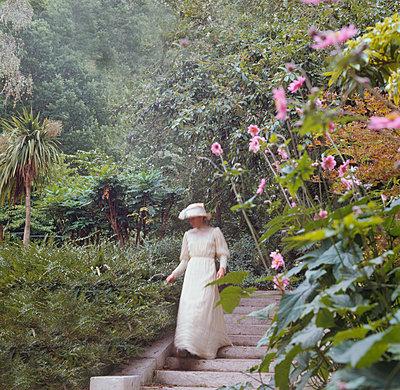 Woman in white dress in garden - p1311m1136869 by Stefanie Lange