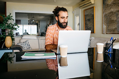 Man working on table at home using laptop - p300m2143867 by Josep Rovirosa