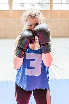 Portrait of confident female boxer in sports hall - p300m2144800 by Stefanie Baum