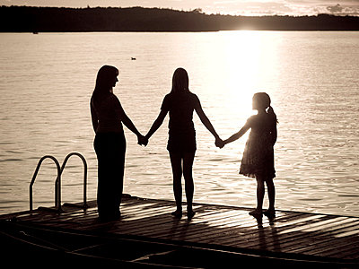 Lake of the Woods, Ontario, Canada; Silhouette of three females on a dock - p4428605f by Design Pics