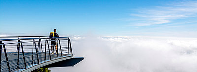 Walker on a viewing platform facing the clouds, Auvergne, France - p813m1082913 by B.Jaubert