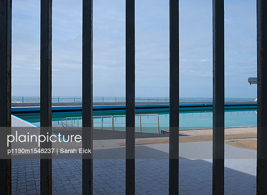 Blick auf einen Swimmingpool am Meer - p1190m1548237 von Sarah Eick