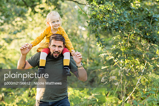 Mature man playing with his little daughter in nature - p300m2156612 by Nicole Matthews