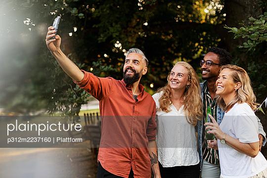 Smiling friends taking selfie - p312m2237160 by Plattform