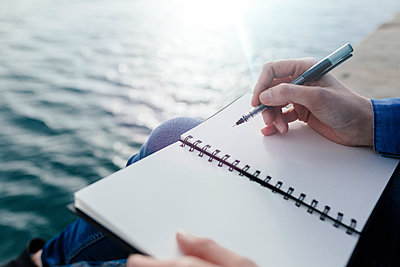 Young woman sitting on dock writing in notebook - p300m1166788 by Boy photography