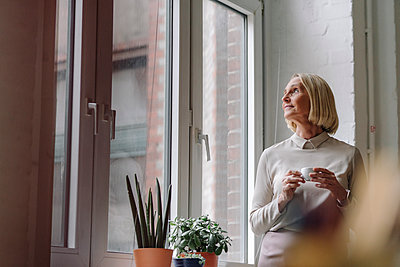 Mature businesswoman having a coffee break at the window in office - p300m2155253 by Gustafsson