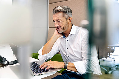 Businessman using laptop while sitting at desk in office - p300m2241535 by Peter Scholl