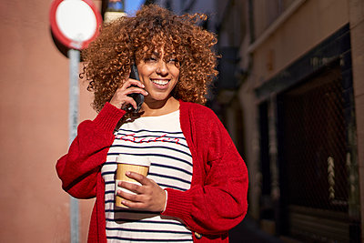 Smiling woman looking away while talking on mobile phone standing outdoors - p300m2257354 by Veam