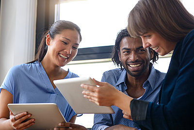 Businesswoman explaining male and female colleague over digital tablet at office - p300m2281529 by Buero Monaco