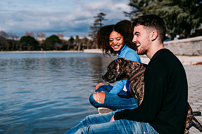 Smiling young couple sitting with dog by lake on sunny day - p300m2281635 by Eva Blanco