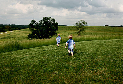Two-year-old twins walk through grass. - p343m963685 by Carmen Troesser
