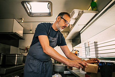 Mature vendor working in food truck - p426m1114875f by Maskot
