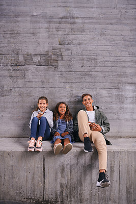 Full length portrait of happy siblings sitting side by side against wall at playground - p426m2074440 by Maskot