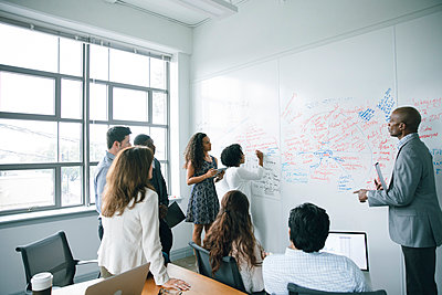 Businesswoman writing on whiteboard in meeting - p555m1504090 by John Fedele