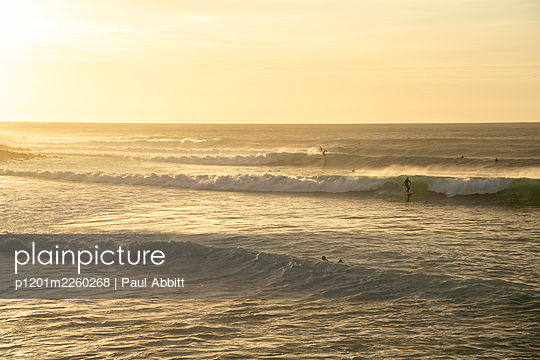 people surfing Indicators with setting sun. - p1201m2260268 by Paul Abbitt