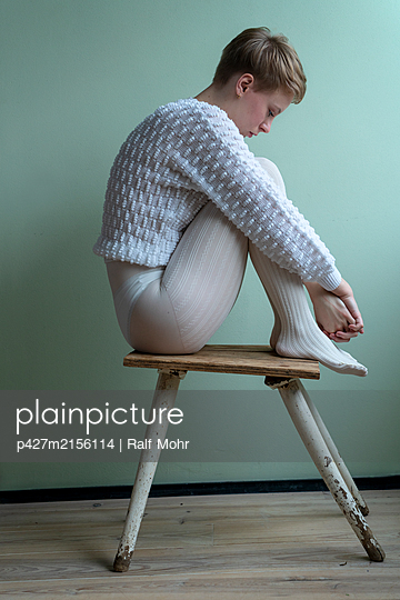 Young woman with short hair on stool - p427m2156114 by Ralf Mohr