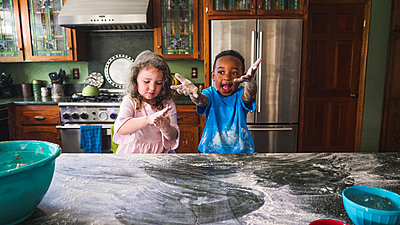 Boy displaying his mess with girl in the kitchen - p1166m2090690 by Cavan Images