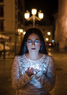 Young woman with lights in hands at night - p1166m2131198 by Cavan Images