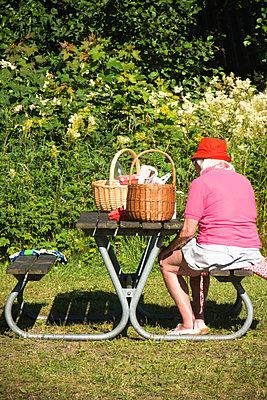 Alte Frau macht ein Picknick - p1418m2002044 von Jan Håkan Dahlström
